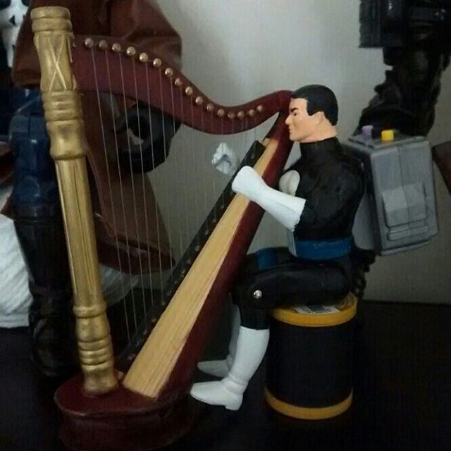 Punisher wearing a backpack while playing his harp.