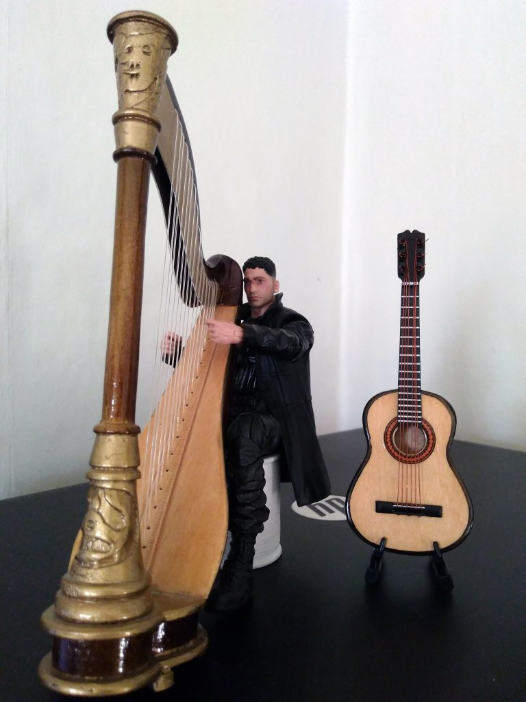Jon Bernthal as The Punisher playing his harp with his guitar by his side.