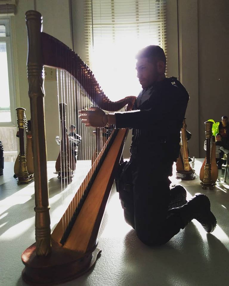 Playing the harp with the harp ensemble and the sun shining through the window.